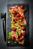 Serrano de Jamon, tomates, salada da rúcula, placa de pedra preta da ardósia Imagem de Stock