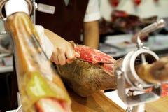 Serrano del jamon o di prosciutto di Parma Chiuda su sulle mani di un cuoco unico che taglia il prosciutto spagnolo italiano trad immagini stock libere da diritti