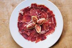 Serrano espagnol de Jamon de nourriture de tapas de cuisine avec la figue Belles tranches d'appétit de viande de porc crue, fond  Photo stock