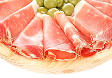 Serrano Ham. Dry cured slices of serrano pork ham with green olives. On wooden plate. On white Royalty Free Stock Photos