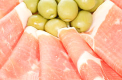 Serrano Ham. Close-up of dried and cured slices of serrano pork ham with green olives. On white Stock Photography