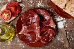 Serrano ham and catalan pa amb tomaquet. High-angle shot of an earthenware plate with some slices of serrano ham and a plate with some slices of typical catalan Royalty Free Stock Photo