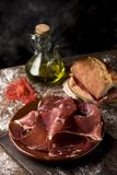 Serrano ham and catalan pa amb tomaquet. A plate with some slices of serrano ham on a rustic wooden table, next to a cruet with olive oil and a sandwich of Royalty Free Stock Photo