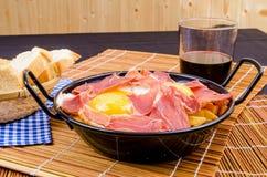 Serrano ham with eggs. Small tapa sized casserole with a serving of serrano ham with eggs Royalty Free Stock Image