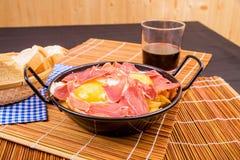 Serrano ham with eggs. Small tapa sized casserole with a serving of serrano ham with eggs Royalty Free Stock Photos