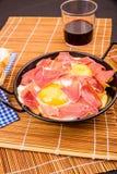 Serrano ham with eggs. Small tapa sized casserole with a serving of serrano ham with eggs Stock Photography