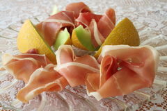 Serrano ham and Galia melon. Appetizer with Spanish Serrano ham and Galia melon on glass plate Royalty Free Stock Photos