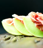 Serrano ham with melon on old wooden table three Royalty Free Stock Photos