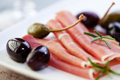 Serrano ham with olives and caper berries Stock Photo