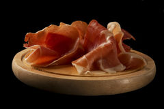 Serrano ham or prosciutto on a wooden plate over black background Stock Photos