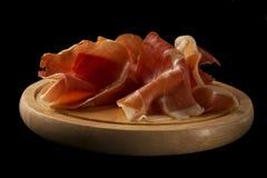 Serrano ham or prosciutto on a wooden plate over black background.  Jamón serrano Stock Photos