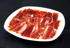 Serrano ham slices on a white dish over black Stock Photos