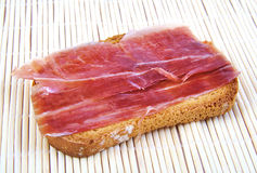 Serrano ham on toasted bread. Jabugo. Spanish tapa. Royalty Free Stock Photos
