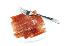 Serrano ham on a white dish with a metal fork. Jabugo. Spanish tapa. Royalty Free Stock Images