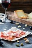 Serrano jamon ветчины или crudo ветчины с отрезанным стеклом трудных сыров красного вина с виноградинами, фисташками Стоковое Фото