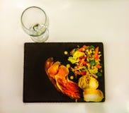 Serrano skinka med grönsaksallad och bröd på den svarta stenen pläterar den tomma vinglaset Arkivfoto