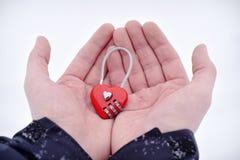 Serratura a combinazione in forma di cuore rossa alle palme dell'uomo Fotografia Stock Libera da Diritti