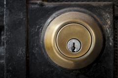 Serratura di porta dorata del metallo con la porta nera fotografia stock libera da diritti