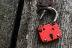 Serratura molto vecchia e rossa che appende sulla parete di legno grigia fotografie stock