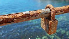 Serratura o lucchetto arrugginita di amore su una sezione del recinto del collegamento a catena immagine stock