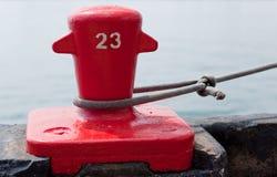 Serre-câble rouge de dock fixant un bateau Images stock