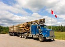 Serre madeira com um guindaste hidráulico que está sendo transportado em Ontário Imagens de Stock