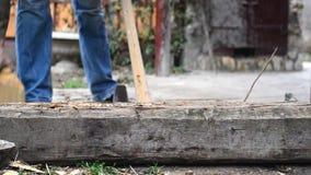 Serre madeira o homem do jaque que desbasta os logs de madeira com machado. vídeos de arquivo
