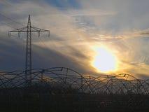 Serres onder lijnen met hoog voltage in de herfstavond royalty-vrije stock afbeeldingen