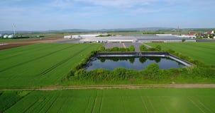 Serresmening van hierboven, Technisch reservoir naast grote serres, groene gebieden rond een grote serre stock videobeelden