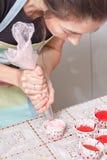 Serrez la crème remplissant sur le petit gâteau Photo libre de droits