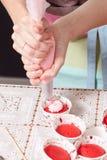 Serrez la crème remplissant sur le petit gâteau Photographie stock libre de droits