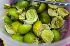 Serrez la peau de citron, citron vert dans la tasse en plastique photographie stock libre de droits