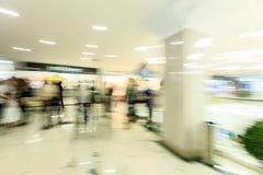 Serrez la précipitation à l'intérieur d'un hall lumineux large moderne de mail avec des boutiques, les viseurs en verre, les gens Photos stock