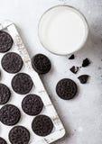 Serrez le biscuit noir se composant de deux gaufrettes de chocolat avec de la crème remplissant de verre de lait sur le fond en p photo stock