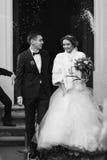 Serrez le riz de jet sur les nouveaux mariés dans l'avant de l'église Images stock