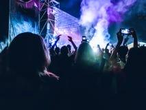 Serrez-vous en soulevant leurs mains et en appréciant la grande partie ou concert de festival image libre de droits