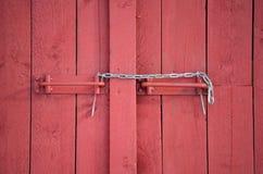 Serrure à chaînes expédient sur la porte de grange rouge photos libres de droits