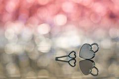 Serrure brillante et clé de coeur en métal à la lumière rouge et à l'arrière-plan de bokeh Images libres de droits