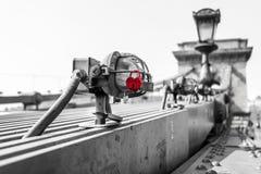 Serrure en forme de coeur rouge accrochant sur la lumière sur un pont à chaînes Photo stock