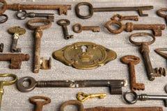 Serrure en laiton entourée par des clés rouillées d'antiquités Photographie stock libre de droits