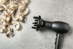 Serrures et dessiccateur de cheveux bouclés sur le fond gris images stock