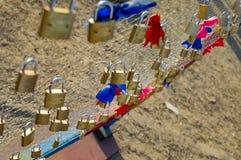 Serrures sur la barrière avec les noeuds rouges et bleus Image stock