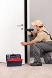 Serrurier installant une serrure de porte photographie stock libre de droits