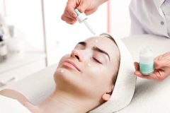 Serum facial treatment of young woman in spa salon Stock Image