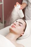 Serum mask spraying from can on young woman's face Stock Images