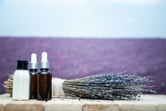 Serum oil and cream of lavender, a stylish set on the background. Lavender field stock photo