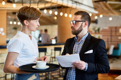 Servant and customer. Helpful servant with tray talking to one of customers in restaurant stock image