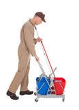 Servant With Washing Bucket And Mop. Full length side view of male servant with washing bucket and mop over white background royalty free stock photo