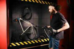 Servar den yrkesmässiga tvagningen av en cykel i seminariet En ung caucasian stilfull man med långt lockigt hår gör en cykelclea arkivfoton