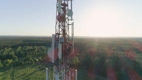 Serve a antena celular, torre da telecomunicação do reparo do trabalhador do técnico na luz solar filme